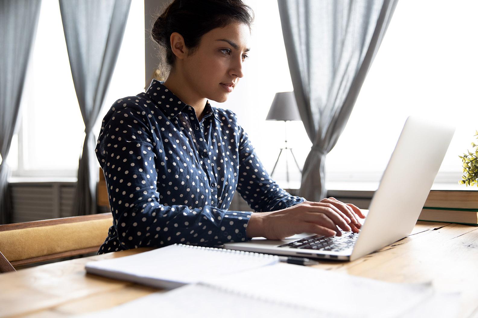 woman typing transcription on laptop