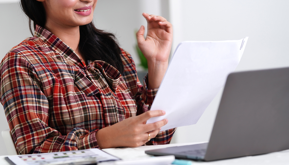 Woman looking at piece of paper with an open laptop