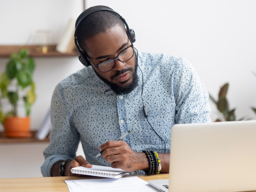 man listening to podcast and transcribing